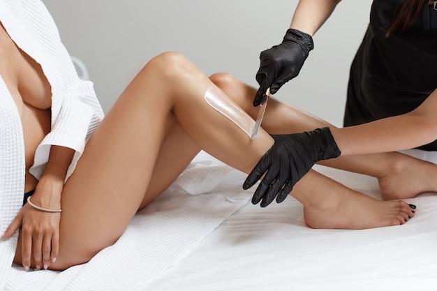 Kosmetikerin macht enthaarung der jungen frau auf ihrem bein mit wachs