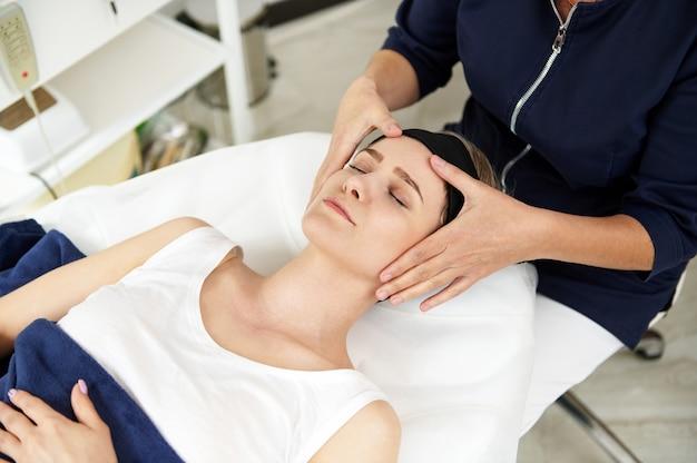 Kosmetikerin macht gesichts-anti-aging-lifting-massage auf dem gesicht der frau in der spa-klinik. professionelle lymphdrainage-massage im modernen spa-center