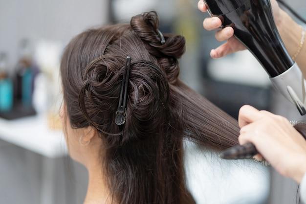 Kosmetikerin macht haare für kunden, sie ist eine schöne frau