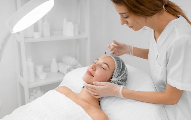 Kosmetikerin macht injektionsfüller auf kundin im salon