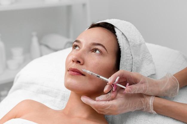 Kosmetikerin macht injektionsfüller auf kundin