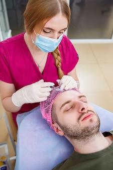 Kosmetikerin macht ultraschall-gesichtsreinigungsverfahren für jungen mann in der klinik. nahaufnahme und handkundenporträt, nahaufnahmeseitenansicht. verfahren im schönheitssalon.