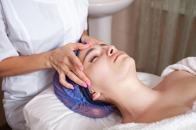 Kosmetikerin massiert das gesicht des kunden