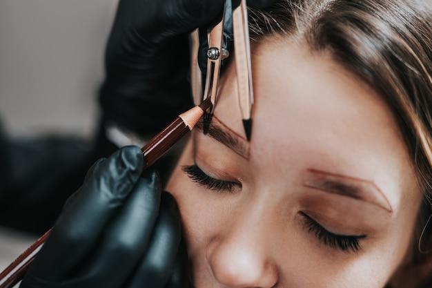 Kosmetikerin misst die proportionen der augenbrauen mit dem lineal. arbeitsablauf bei der mikropigmentierung in einem schönheitssalon.