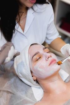 Kosmetikerin mit einem pinsel trägt eine weiße feuchtigkeitsmaske auf das gesicht einer jungen kundin in einem spa-schönheitssalon auf