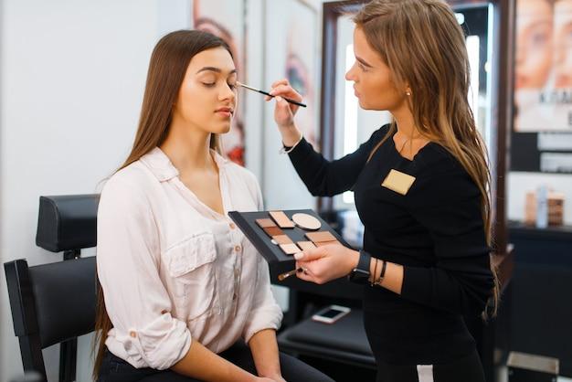 Kosmetikerin mit pinsel und frau im kosmetikgeschäft. luxus-schönheitssalon, kundin und kosmetikerin im modemarkt