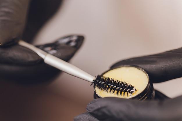 Kosmetikerin mit produkt für augenbrauen