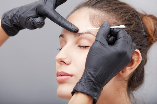 Kosmetikerin permanent make-up auf die augenbrauen auftragen