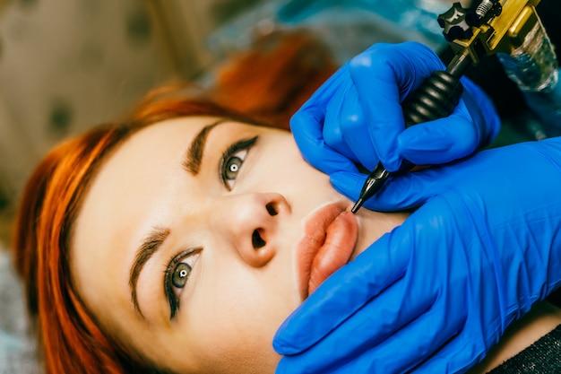 Kosmetikerin permanent make-up auf die lippen anwenden. junge frau, die verfahren des dauerhaften lippenmake-ups im tätowierungssalon, nahaufnahme durchmacht