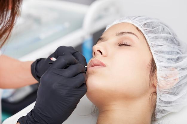 Kosmetikerin permanent make-up auf die lippen auftragen