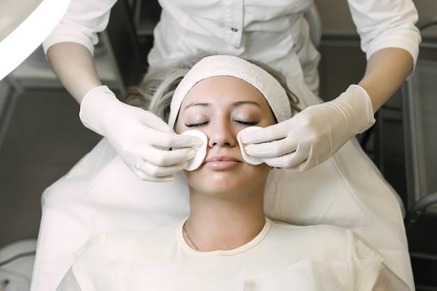 Kosmetikerin reinigt die haut des patienten mit einem wattepad