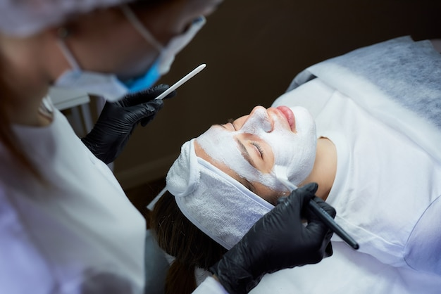 Kosmetikerin seitenansicht, die sanft peeling gommage auf das gesicht des mädchens aufträgt