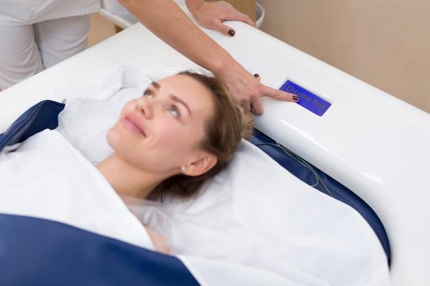Kosmetikerin startet hydromassage im spa. professionelle moderne kosmetologie. körperpflege. der prozess des hydromassagebades in der kosmetikklinik.