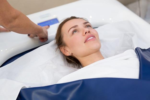 Kosmetikerin startet hydromassage im spa. professionelle moderne kosmetologie. körperpflege. prozess des hydromassage-bades in der kosmetikklinik.
