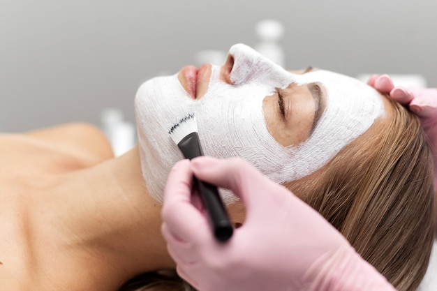 Kosmetikerin trägt eine gesichtsmaske aus weißem ton mit einem pinsel auf das gesicht einer frau auf