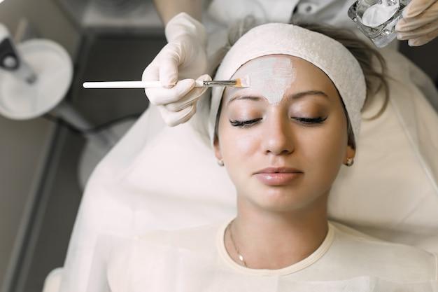 Kosmetikerin trägt kosmetisches produkt mit pinsel auf patientin auf