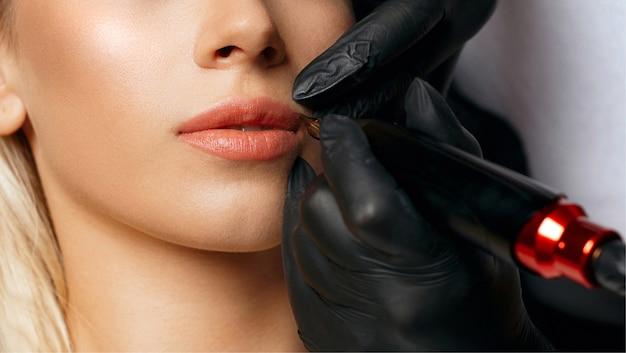 Kosmetikerin trägt permanentes pigment auf die lippen einer frau auf
