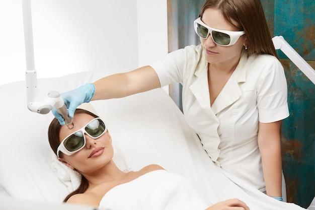 Kosmetikerin trägt weiße robe, die gesichtsbehandlungen mit laser im schönheitssalon für attraktive frau in schutzbrille macht