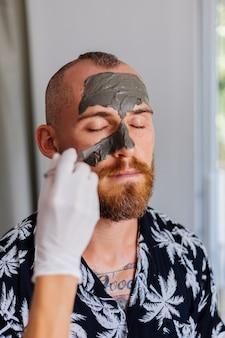 Kosmetikerin tragen tonmaske mit pinsel auf gesicht des jungen gutaussehenden mannes in der schönheitsklinik auf