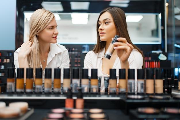 Kosmetikerin und frau, die nagellack an der vitrine im kosmetikgeschäft wählen. luxus-schönheitssalon, kundin und kosmetikerin im modemarkt