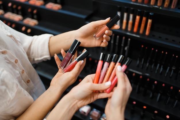 Kosmetikerin und frau hält nagellack an der vitrine im kosmetikgeschäft. luxus-schönheitssalon, kundin und kosmetikerin im modemarkt