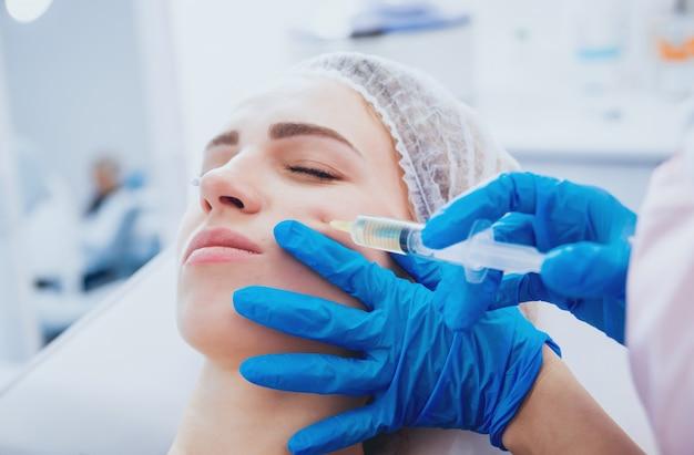 Kosmetikerin und patientin in der klinik für ästhetische medizin erhalten eine behandlung