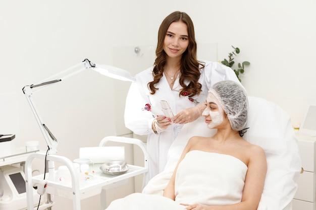 Kosmetikerin und patientin in medizinischer mütze und maske in der klinik