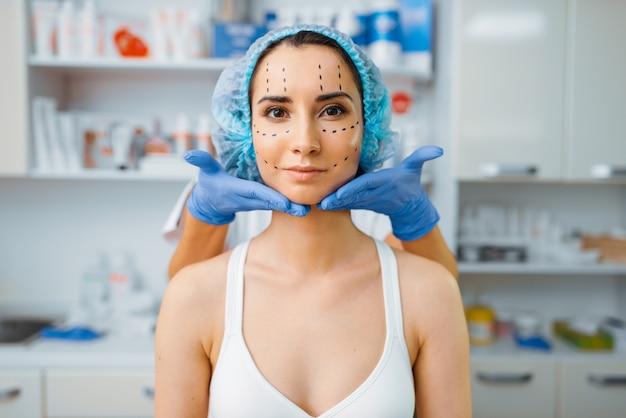Kosmetikerin und patientin mit markern im gesicht