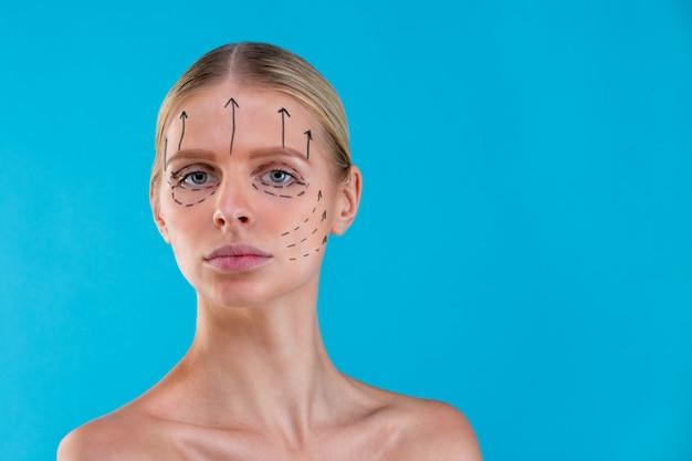 Kosmetikerin zeichnet korrekturlinien auf frauengesicht. vor der operation der plastischen chirurgie. auf blau isoliert