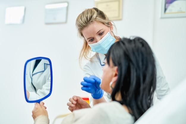 Kosmetikerin zeigt dem mädchen das ergebnis der hautpflege
