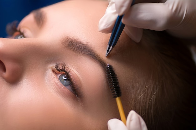 Kosmetikerin zupft augenbrauen. augenbrauenpflege in einem schönheitssalon.