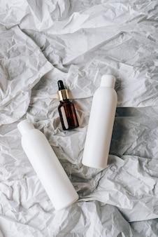 Kosmetikflaschen auf weißem zerknittertem papier
