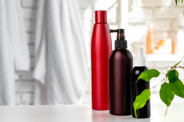 Kosmetikflaschen gegen weißen badezimmerwandhintergrund