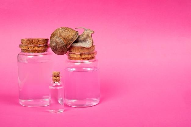 Kosmetikflaschen mit dem zusatz von schneckenmucin, mockup natürlicher hautpflegeschönheit auf rosafarbenem hintergrundkopierraum.