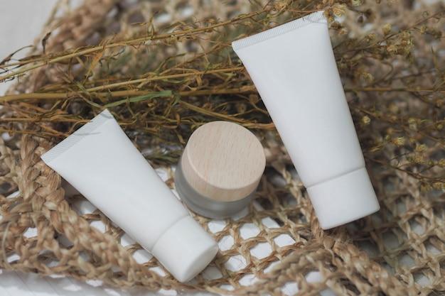 Kosmetikflaschenbehälter weiß, cremefarbenes produkt mit trockener blume und gewebten handtaschen.