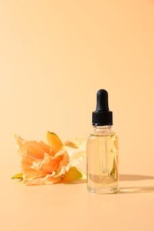 Kosmetiköl oder essenz in glasflasche mit frischen lilienblumen auf beigem raum