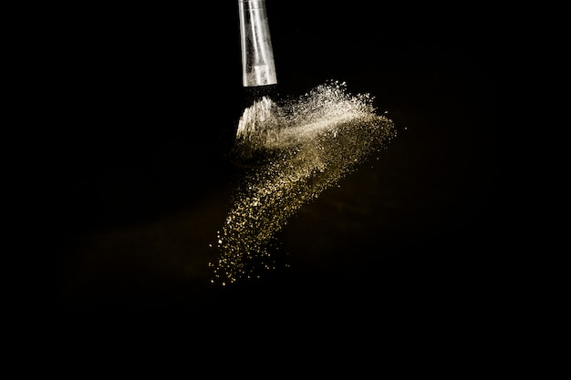 Kosmetikpinsel mit goldenem kosmetischem puderausbringen