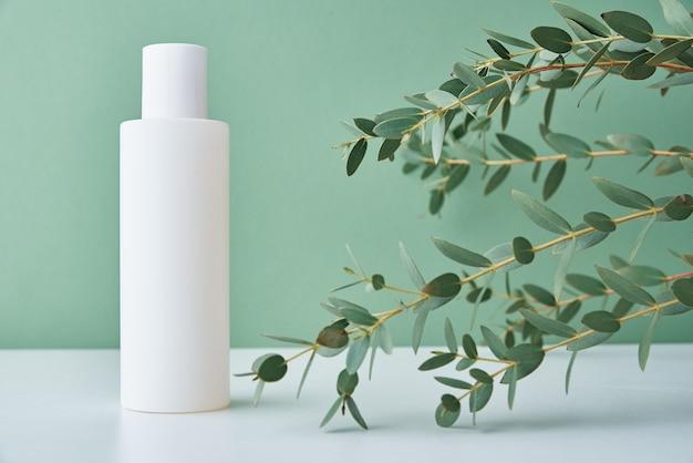 Kosmetikprodukt der schönheit in der weißen flasche auf grünem hintergrund. natürliche bio-kosmetik