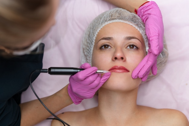 Kosmetikschrank kunde liegt auf der couch. kosmetikerin markiert die lippen. vorbereitung für das dauerhafte lippen-make-up. nahansicht. schönheitsindustrie