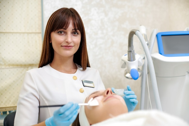 Kosmetikspezialist, der eine gesichtsmaske mit einem pinsel auf das gesicht aufträgt. schönheitsbehandlung. hautpflege.