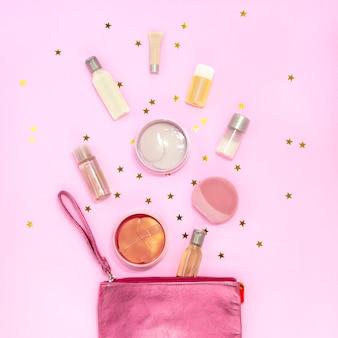 Kosmetiktasche mit make-up-produkten, cremetiegeln, gelflaschen, silikon-gesichtsreinigungsbürste, hydrogel-augenklappe auf rosa mit goldenen sternen