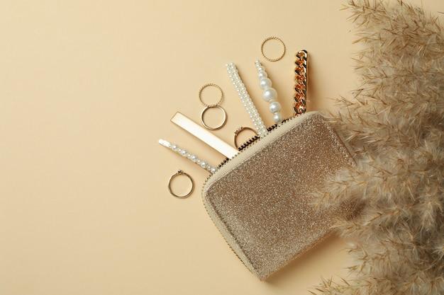 Kosmetiktasche mit schmuck und schilf auf beigem hintergrund