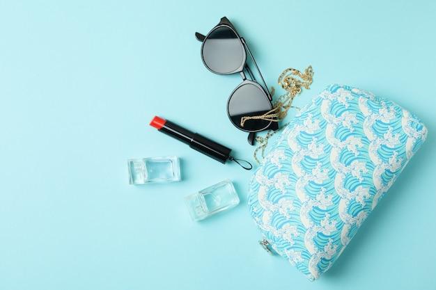 Kosmetiktasche und weibliches zubehör auf blauem hintergrund