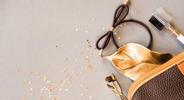 Kosmetiktasche, wimperlockenwickler, brauenbürste auf glänzendem beige hintergrund. beauty-konzept. flaches lay-design.