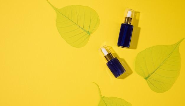 Kosmetische blaue glasflaschen mit einer pipette auf gelbem grund. kosmetik-spa-branding-modell, ansicht von oben