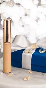 Kosmetische branding weihnachtsglitter und girly blog konzept urlaub make-up foundation basis concealer und blaue geschenkbox luxuskosmetik vorhanden und blanko-etikettenprodukte für beauty brand design