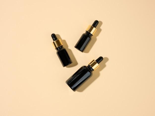 Kosmetische braune glasflaschen mit pipette auf beigem hintergrund. kosmetik-spa-branding-modell, ansicht von oben
