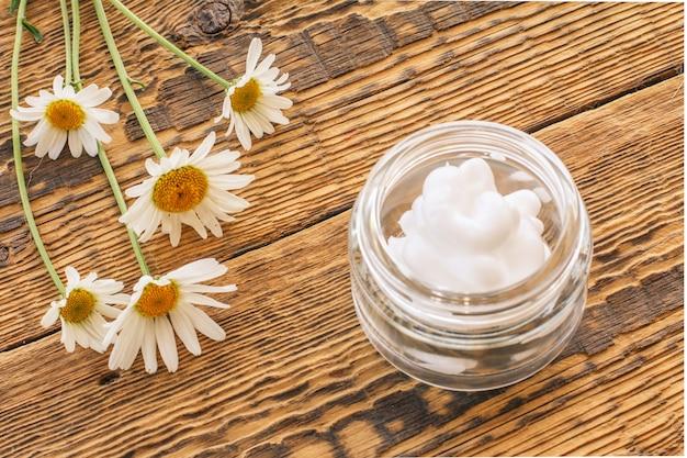 Kosmetische creme in einem glasgefäß und frische kamillenblüten auf holzbrettern. ansicht von oben.