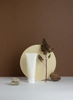 Kosmetische creme in einer tube auf einem braunen hintergrund. naturkosmetik. hautpflege. attrappe, lehrmodell, simulation. speicherplatz kopieren.