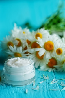 Kosmetische creme mit kamillenblume oder einem körper und einem gesicht auf blauem holztisch